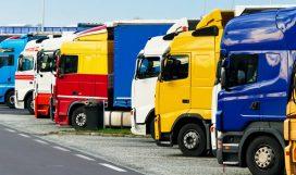 Viele verschiedene LKWs parken auf einem Parkplatz der Autobahn